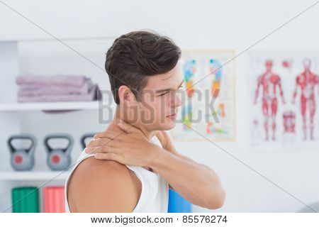 Young man suffering from shoulder pain in medical office