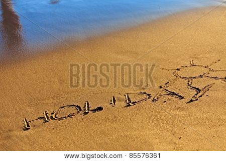 Holiday text drawn in sand on a sunny summer day.