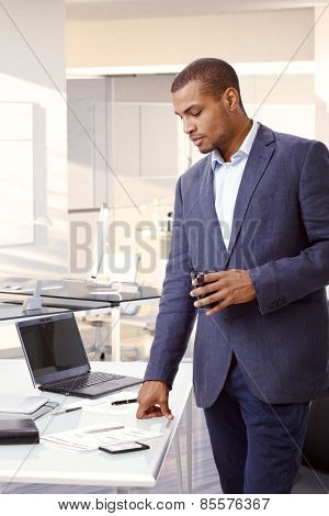 Young black businessman standing by desk in office, looking at papers, drinking tea.