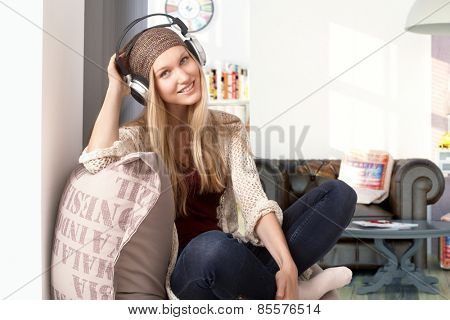 Happy young girl listening to music through headphones at home, smiling, looking at camera.