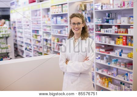 Portrait of a smiling pharmacist in lab coat with arms crossed in the pharmacy