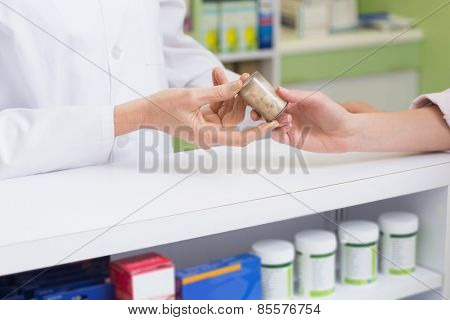 Pharmacist and costumer holding medicine jar at pharmacy