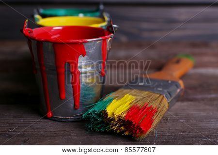 Metal buckets with colorful paint near brush on wooden background