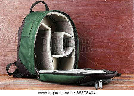 Backpack for camera on wooden background
