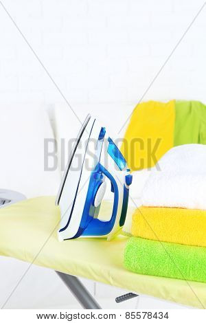 Iron with towels on ironing board on light home interior background