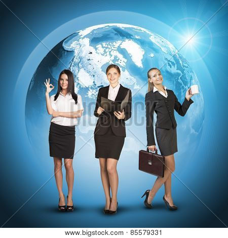 Business womens in suits, blouses, skirts, smiling and looking at camera. Against background of glob