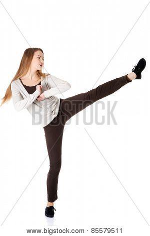 Full length blonde woman kicking
