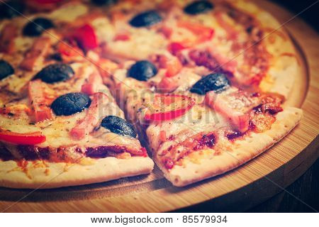 Vintage retro effect filtered hipster style image of sliced ham pizza with capsicum and olives on wooden board on table