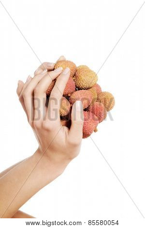 Close up on female hand holding lychees.