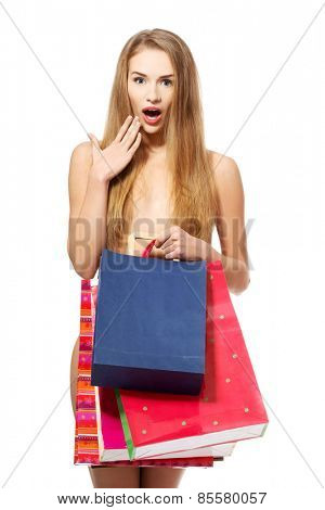 Nude woman holding full of shopping bags.