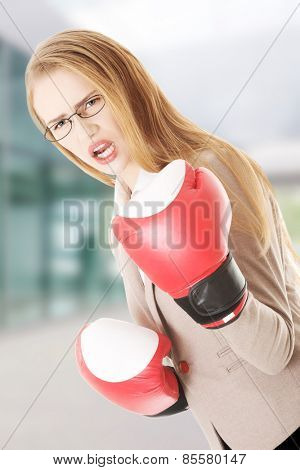 Beautiful business woman with boxing gloves