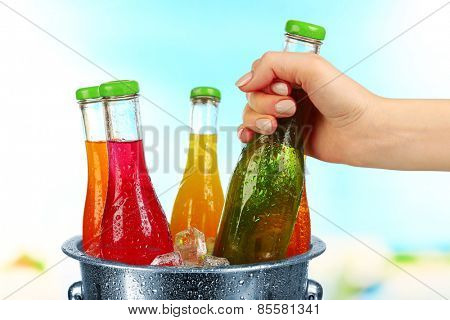 Female hand taking glass bottle of drink from metal bucket on bright background