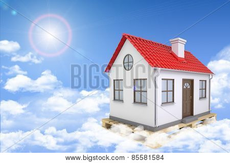 White house with red roof and chimney  in clouds. Background sun shines brightly