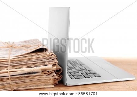 Laptop with stack of newspapers on table isolated on white