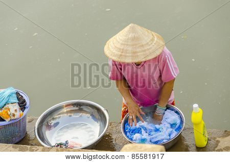 CHAU PHONG, VIETNAM, JANUARY 3, 2013: Local woman washes on riverside of Hau River (Bassac River) in Mekong Delta