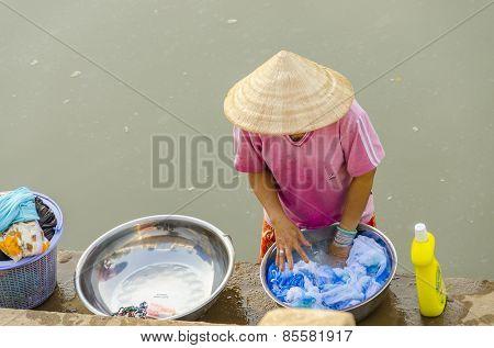 CHAU PHONG, VIETNAM, JANUARY 3, 2013: Local woman washes on riverside of Hau River (Bassac River) in Mekong Delta