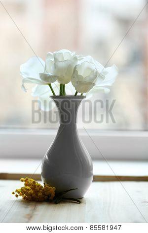 Beautiful tulips in vase on windowsill