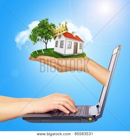 White house in hand for sale with red roof, crown, chimney of screen laptop. Background sun shines b