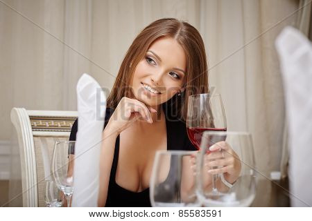 Smiling woman drinking aperitif in restaurant
