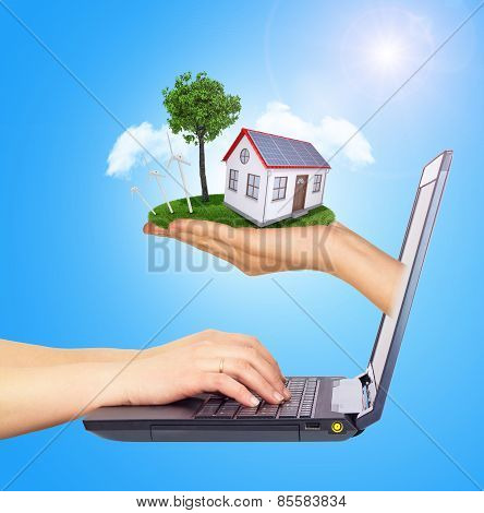 Hand holding house on green grass with tree, solar panels, wind turbine of screen laptop. Background