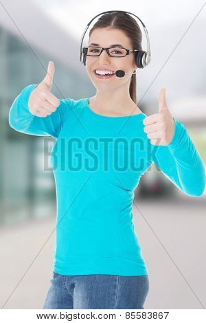 Young casual woman with headphones and microphone showing ok