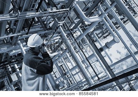 oil worker pointing at giant pipelines construction inside refinery details