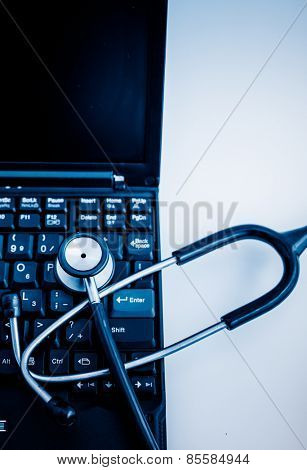 Electronic medical, stethoscope on PC/Laptop/Keyboard blue toned images.