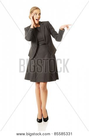 Portrait of amazed businesswoman holding hands on chin.
