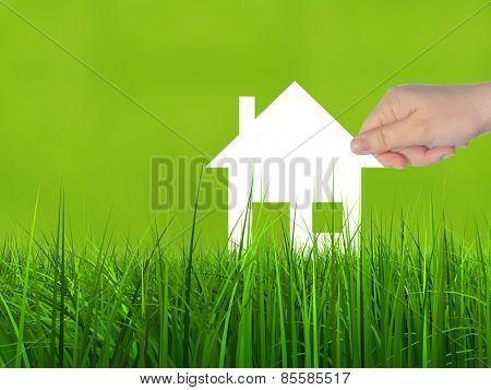 Concept or conceptual white paper house symbol held in hand by a woman in green summer grass background