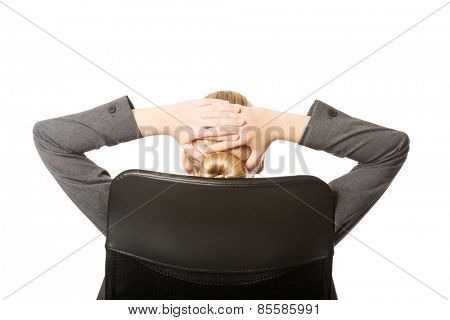Businesswoman resting on armchair holding her neck