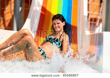 Happy woman in bikini sliding water park.