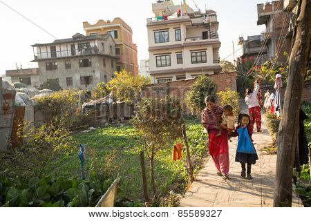 KATHMANDU, NEPAL - CIRCA DEC, 2013: Unidentified local people near their home in a poor area of the city. The caste system is still intact today but the rules are not as rigid as they were in the past