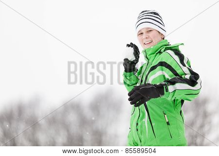 Playful Young Boy Taking Aim With A Snowball