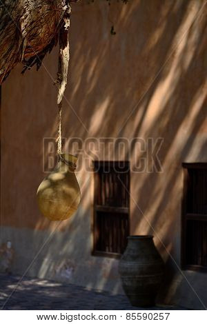 Pottery Hangs From A Tree In A Shady Inner Courtyard