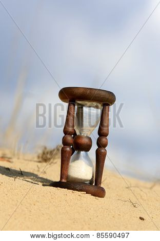 Hourglass in sandy desert at sunny day