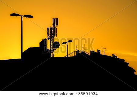 Roofs Of Buildings With Many Antennas In A Big City At Sunset Make Silhouettes