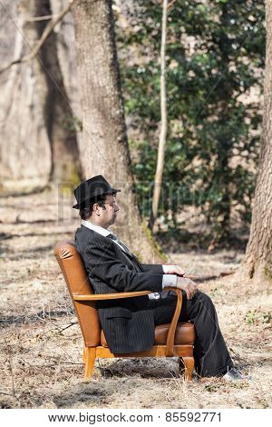 man alone in the woods sitting on a armchair, side view