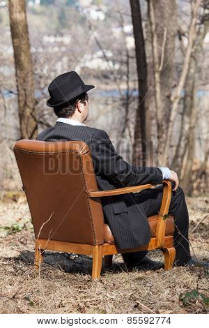 man alone in the woods sitting on a armchair, rear view