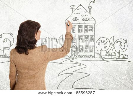 Mature good looking woman drawing sketch of the house