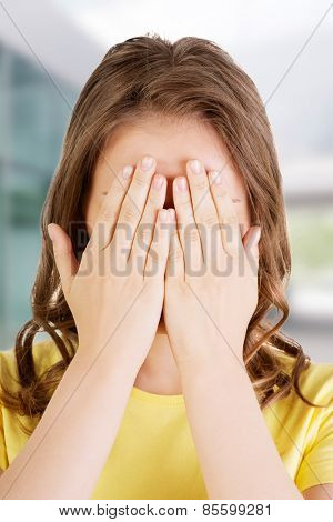 Young teen woman covering her face with hands.