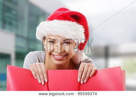 Beautiful woman wearing santa hat, holding shopping bag