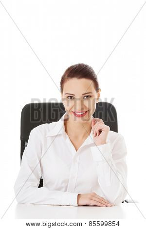 Happy businesswoman sitting at the desk.