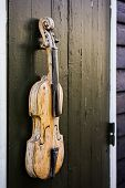 stock photo of violin  - Old and trashed vintage violin hanging outside on a wooden wall - JPG