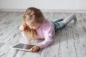 image of lie  - Child with tablet lying on floor - JPG