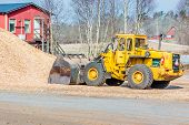 foto of wheel loader  - Yellow front loader with bucket down scooping wood chips for biofuel - JPG