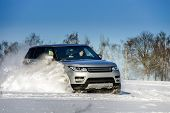 image of snow-slide  - Powerful 4x4 offroader car running on snow field winter day transport concept - JPG