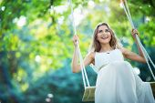 image of swing  - Smiling young woman on a swing - JPG