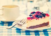 image of dessert plate  - Vintage retro effect filtered hipster style image of dessert fruit cheese cake on plate with fork and coffee cup on blue checkered tablecloth - JPG