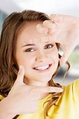 stock photo of woman red blouse  - Smiling woman wearing red blouse is showing frame by hands - JPG