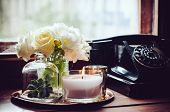 stock photo of vase flowers  - Bouquet of white flowers in a vase, candles on a copper vintage tray, old rotary phone, retro home decor